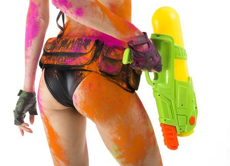 loco: Feliz celebración Festival de Holi! Parte de color loco - Mujer atractiva de bello cuerpo, culo y las piernas. Chica en bikini con cuerpo perfecto y la pistola de juguete de color brillante multicolor de pintura en polvo en blanco. Festival en Goa