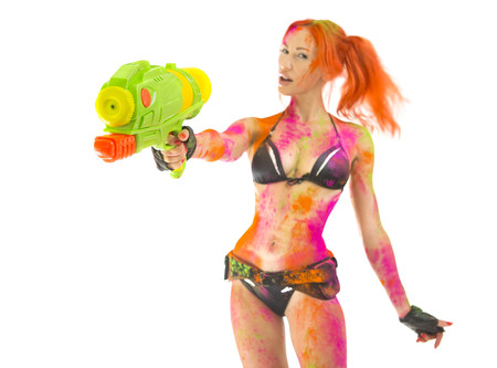 Happy Holi Indian Festival Celebration! Crazy Party game in Goa. Beautiful Sexy joyful Girl in bikini colored Dry Bright Multicolor Paint Powder targets the gun, White background. Emotional hot woman