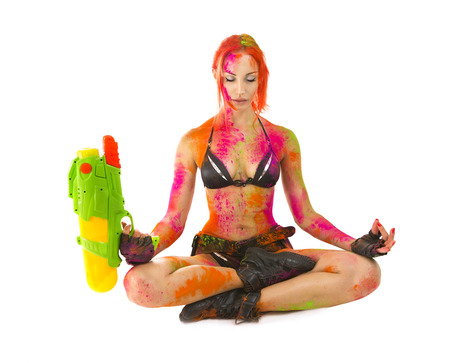 Happy Holi Indian Festival Celebration! Beautiful Sexy joyful Girl in bikini colored Dry Bright Multicolor Paint Powder with toy gun relaxing after Paintball Crazy Party game on White. Hot woman meditate