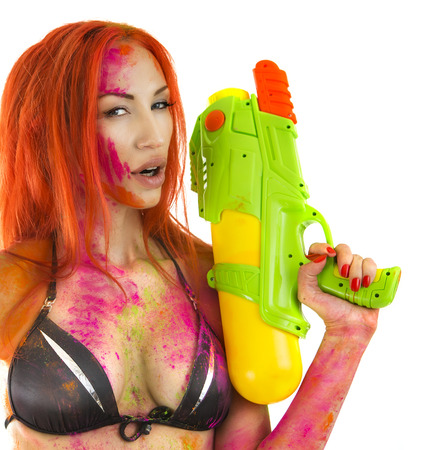watergun: Happy Holi Indian Festival Celebration! Crazy Party in Goa - Beautiful Sexy joyful Girl in bikini with toy gun colored Dry Bright Multicolor Paint Powder on White background. Emotional woman