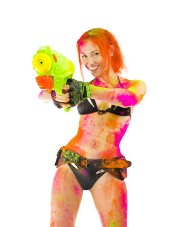 watergun: Happy Holi Indian Festival Celebration! Paintball Crazy Party game. Beautiful Sexy joyful Girl in bikini colored Dry Bright Multicolor Paint Powder targets the gun on White. Emotional hot woman