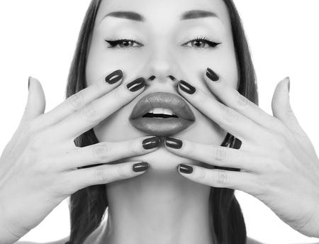 labios sensuales: Sexy morena joven y bella chica con un maquillaje - Las uñas y lápiz labial. Retrato del encanto femenino, los labios brillantes sensual. El maquillaje y la manicura de primer plano. Jóvenes look de moda de moda. Fondo blanco Foto de archivo