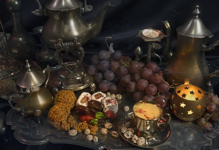 Still Life. Traditional Oriental Sweets on Vintage Moroccan Tray. Cup of Saffron Tea, indian spices. Gala dinner by candlelight. Arab, African, Turkish, Persian, Indian silver dishes, Kitchen Utensils