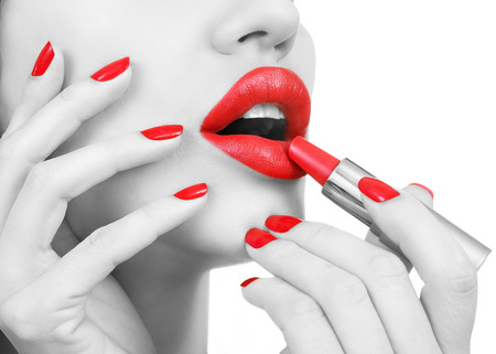 female sexuality: Black and White female Portrait with Red lips. Sexy Young Beautiful Girl with Red Nails applies red lipstick. Female Glamour portrait, sensual bright Make-up and Manicure closeup. White background Stock Photo