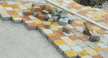 pavement: Laying Paving Slabs by mosaic close-up. Road Paving, construction. Repairing sidewalk. Workers laying stone paving slab. Laying colored tiles in a city park (garden). Fixed tessellated sidewalk tile