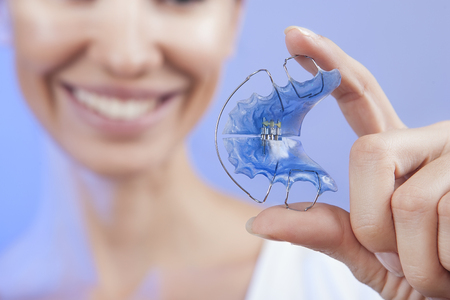 crooked teeth: Dental and Ortho - Beautiful Smiling Girl Holding Retainer for Teeth (Braces for Teeth). Stomatology Orthodontics Dental Theme, Methods of Teeth (Bite) Correction and fix. White Smile Close-up. Stock Photo