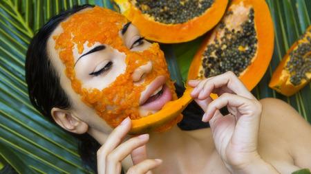 Beautiful caucasian Woman Having fresh Papaya natural facial mask apply. Papaya Peeling. Skin care and Wellness (outdoors). Facial vitamin mask of papaya slices at spa salon. Antioxidant cosmetic Stock Photo