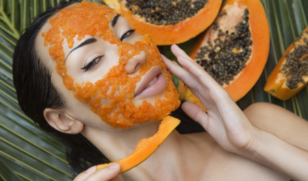 Beautiful caucasian Woman Having fresh Papaya natural facial mask apply. Papaya Peeling. Skin care Beauty and Wellness outdoors. Facial vitamin mask of papaya slices at spa salon.