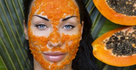 Beautiful caucasian Woman Having fresh Papaya natural facial mask apply. Papaya Peeling. Skin care and Wellness (outdoors). Facial vitamin mask of papaya slices at spa salon. ?ntioxidant cosmetic