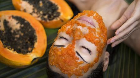 the caucasian beauty: Beautiful caucasian Woman Having fresh Papaya natural facial mask apply. Papaya Peeling. Skin care Beauty and Wellness outdoors. Facial vitamin mask of papaya slices at spa salon.