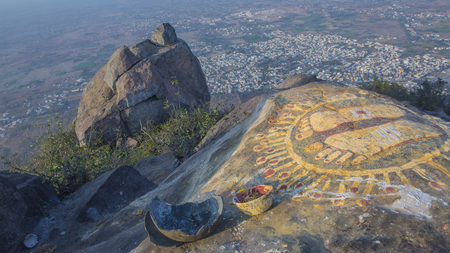 A stone with the image of the footprints of a guru on top of a mountain Arunachala. Top view of the Tiruvannamalai city and Arunacheshvara Shiva Temple from Arunachala hill. Holy hill in Tamil Nadu. Stock Photo