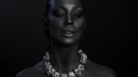 Halloweennacht. Horror-Party Schöne reizvolle junge vamp Frau mit mystischem Make-up. Schreckliche schwarze Göttin Kali. Mädchengesicht im dunklen Licht mit den Schädeln. Wütende Lilith Standard-Bild - 89007549