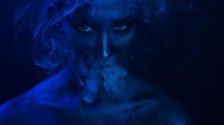 할로윈 Vape 파티, 유흥. 아름 다운 섹시 한 젊은 여자 매혹적인 신비로운 메이크업 나이트 클럽에서 vaping, 연기를 내뿜는. 클럽에서 기화 기 여자 흡연입니다. 푸른 신비한 연기 스톡 콘텐츠 - 90359020