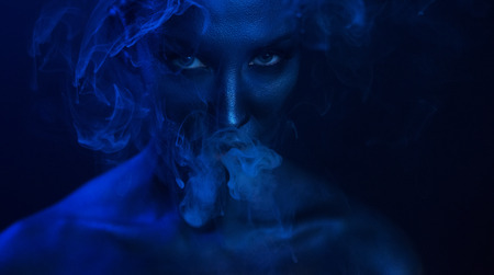 Halloween Vape Party, Nightlife. Beautiful Sexy Young Woman with glamorous mystical makeup vaping in Nightclub, exhaling smoke. Girl smoking vaporizer in Club. Blue mystic smoke