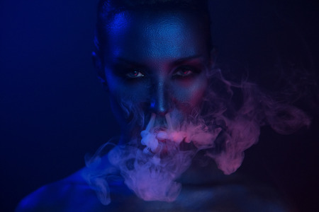 Halloween night. Horror Vape Party. Beautiful Sexy Young vamp Woman with glamorous mystical makeup vaping in Nightclub (exhaling smoke). Girl smoking in Club. Blue mystic smoke