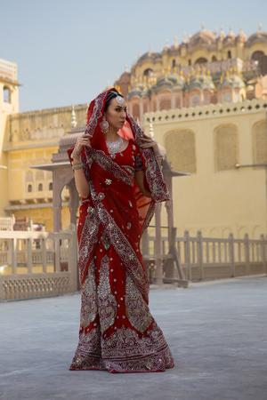 Indian Woman in Red bridal Sari clothing with oriental jewelry. Beautiful Indian Bride Girl in Wedding Sari. Indian near the Hawamahal palace. Indian Maharani at the Hawa Mahal. Eastern tale