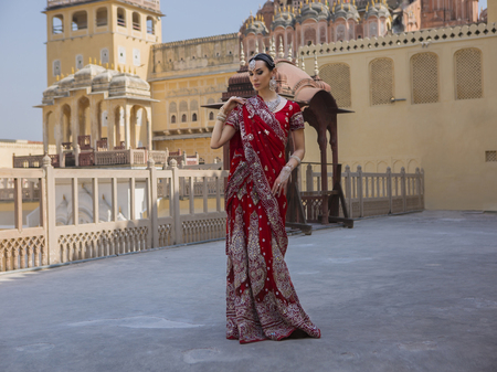 Indian Woman in Red Bridal Sari clothing with bridal oriental wedding jewelry. Beautiful Maharani. Beautiful Girl in wedding Sari. Indian Bride in oriental Palace Hawa Mahal