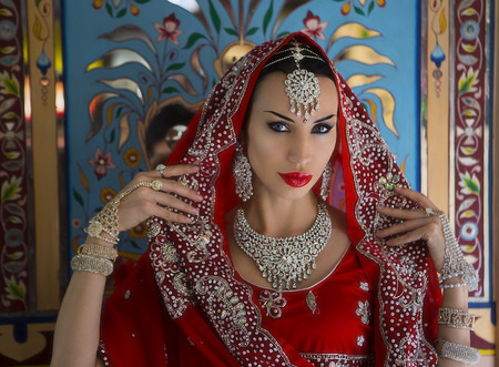 Young Indian Woman in Red bridal Sari clothing with bridal oriental jewelry. Beautiful Indian Girl in Wedding Sari. Indian Bride near the palace. Wedding day. Indian Maharani. Eastern tale