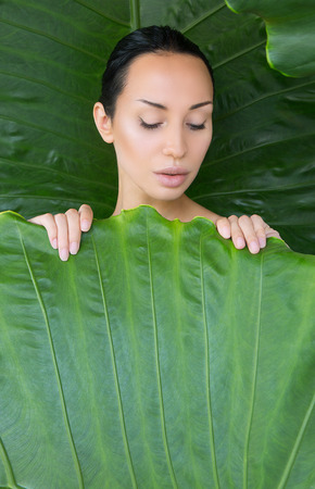 Soft bed of leaves. Portrait of beautiful young woman looking trough green tropical leaves. Young woman's face surrounded by tropical leaves. Natural creative bed linen, bedclothes. Wellness. Space for text