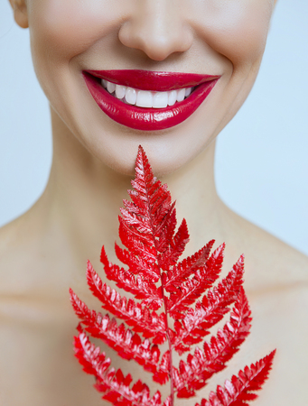 Smile with healthy tooth. A woman with red lips and a fern. Woman's mouth with Sexy red Lips. Female portrait with bright Lip gloss.Dental concept 版權商用圖片