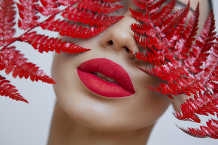 A woman with Sensual red lips and a fern. Woman's mouth with Sexy red Lips. Sexy woman matt Red Lips on a Gray background. Female portrait with bright makeup. matt lipstick 版權商用圖片