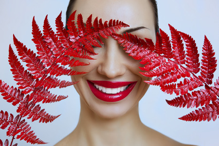 A woman with Sensual red lips and a fern. Woman's mouth with Sexy red Lips. Sexy woman Red Smiling Lips on a Gray background. Female portrait with bright makeup. Lip gloss
