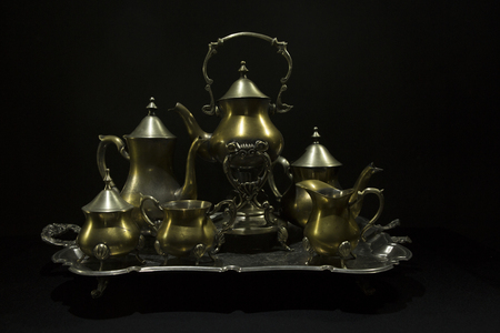 Antique service. Antiques on an old silver tray on a dark background. Beautiful Antique silver plated tea-set on the table.