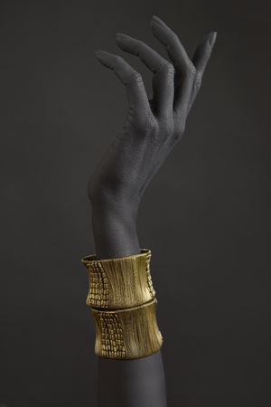 Black woman's hand with gold jewelry. Oriental Bracelets on a black painted hand. Gold Jewelry and luxury accessories on black background closeup. High Fashion art concept  版權商用圖片