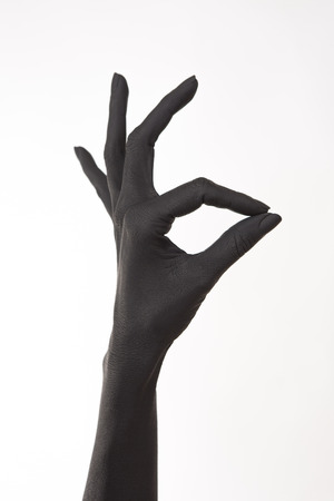 Ok sign. Hand okay gesture. Black painted woman's hand giving a ring sign.