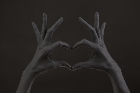Black painted woman's hand doing heart symbol. Symbol of love, declaration of love. Woman Doing heart shape with hand and fingers. Feelings. unrequited love