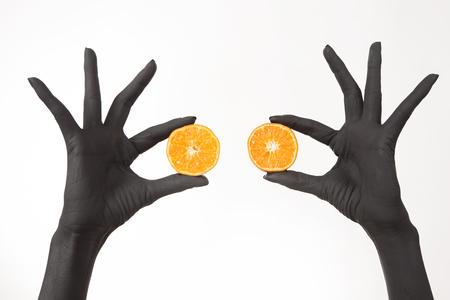 Black woman's hands holding orange halves. Black hands with bright tasty mandarin. Creative colorful art concept. Vitamins and good mood. Summer detox diet 版權商用圖片