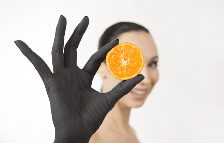 Black woman's hand holding orange halves near her face. Black hand with bright tasty mandarin. Creative colorful art concept. Portrait of a young woman. Summer detox