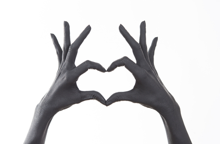 Black painted woman's hand doing heart symbol. Symbol of love, declaration of love. Woman Doing heart shape with hand and fingers. Feelings. unrequited love. 版權商用圖片