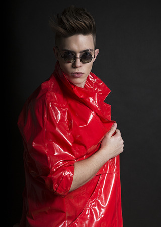 Young man's portrait. Stylish handsome sexy Guy in fashionable red lacquer raincoat, Close-up face with round sunglasses. Street Style. Trendy youthful male look. Man in Red trench.