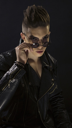 Young man's portrait with round sunglasses. Stylish handsome sexy boy in black leather fashionable rocker-style jacket, Close-up face. Rocker, street Style. Trendy rock 'n' roll male look 版權商用圖片
