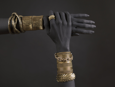 Black woman's hands with gold jewelry. Oriental Bracelets on a black painted hand. Gold Jewelry and luxury accessories on black background closeup. High Fashion art concept 版權商用圖片