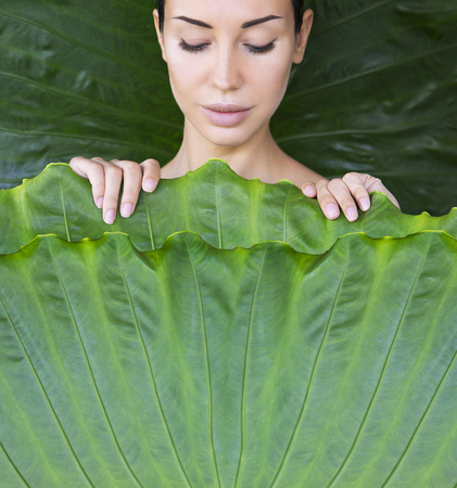 Young woman's face surrounded by tropical leaves. The girl is covered with leaves, bed of leaves. Woman face with Natural nude make-up on a tropical leaf background. Natural cosmetic and wellness concept. Space for text 版權商用圖片