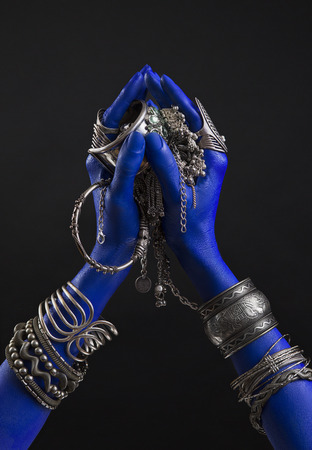 Blue woman's hand with indian Silver jewelry. Oriental Bracelets on a hand. Silver Jewelry and luxury accessories on black background closeup. Asian Fashion art concept 版權商用圖片