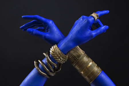 Blue woman's hands with indian gold jewelry. Oriental Bracelets on a hand. Gold Jewelry and luxury accessories on black background closeup. Asian Fashion art concept 版權商用圖片