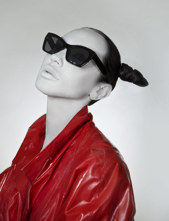 Creative glamor. Young Woman In fashionable red Long lacquer raincoat and sunglasses. Crazy Fashion Make-up, Accessory and Creative Hairstyle. Stylish demon, Total black look. Girl with white face. 版權商用圖片