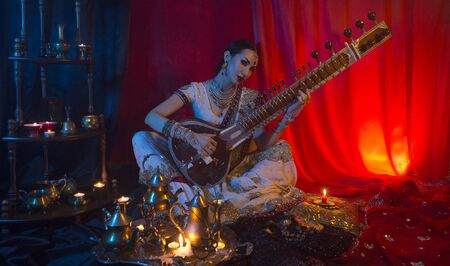 Beautiful young indian woman in traditional Sari clothing with Oriental Jewelry Playing the Sitar. Indian woman Playing night Raga the Sitar, Eastern Music. Musical Candlelight Party in India. 版權商用圖片