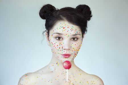 Young pretty girl treating the cat with candy. Portrait of a young girl with Confectionery Topping on her face, Sweetie girl. Cat licking candy.