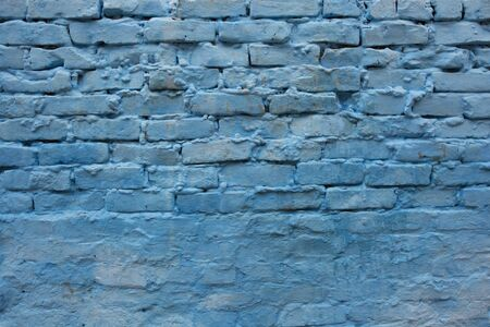 Blue brick wall of the old house. Textured background. Cracked concrete vintage brick wall background, old wall painted blue.