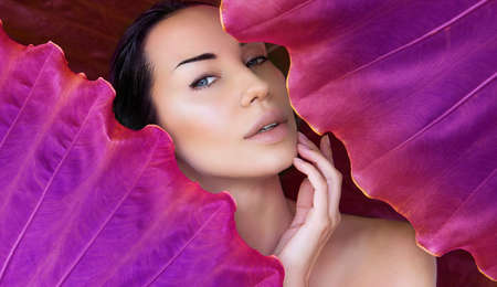 Young woman's face surrounded by Colored tropical leaves. Woman face with Natural nude make-up on a Pink tropical leaf background. Natural cosmetic and wellness. Purity and skincare. Space for text