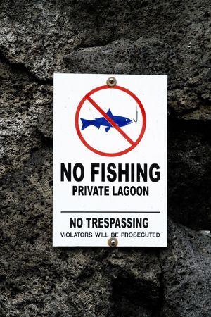 A no fishing sign on lava rocks photo