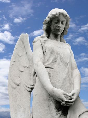 headstone: An angel scuplture with a blue sky background.