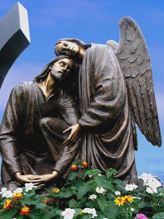 angel de la guarda: Una escultura de bronce religiosas con un cielo azul de fondo.