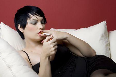 malign: Woman smoking a cigarette on white sofa.