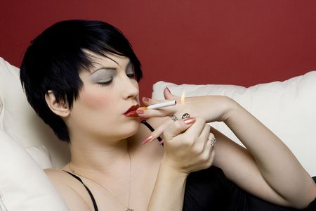 sleazy: Woman smoking a cigarette on white sofa.