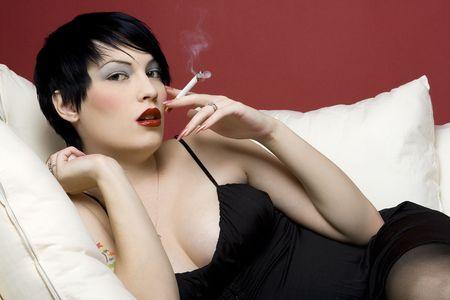 maligno: Mujer de fumar un cigarrillo en blanco sof�.  Foto de archivo
